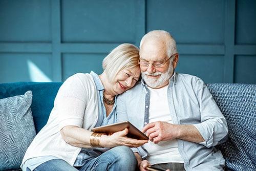 Zwei Personen sitzen auf dem Sofa, mit einem Tablet in der Hand.
