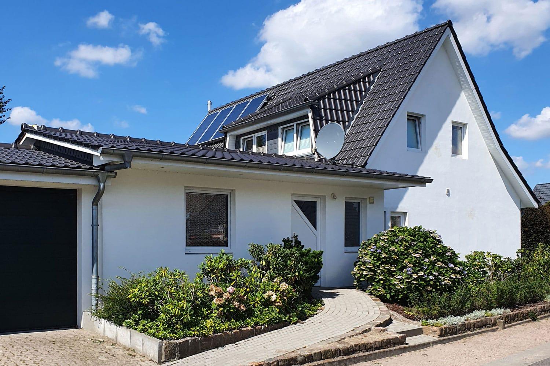 Ein modernes weißes Haus mit einem blauen Dach und einer Garage.