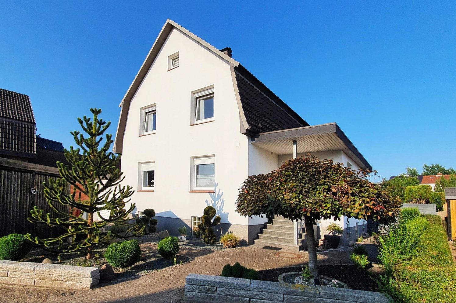 Weißes Haus mit zwei Bäumen und vielen kleinen Pflanzen im Vorgarten.