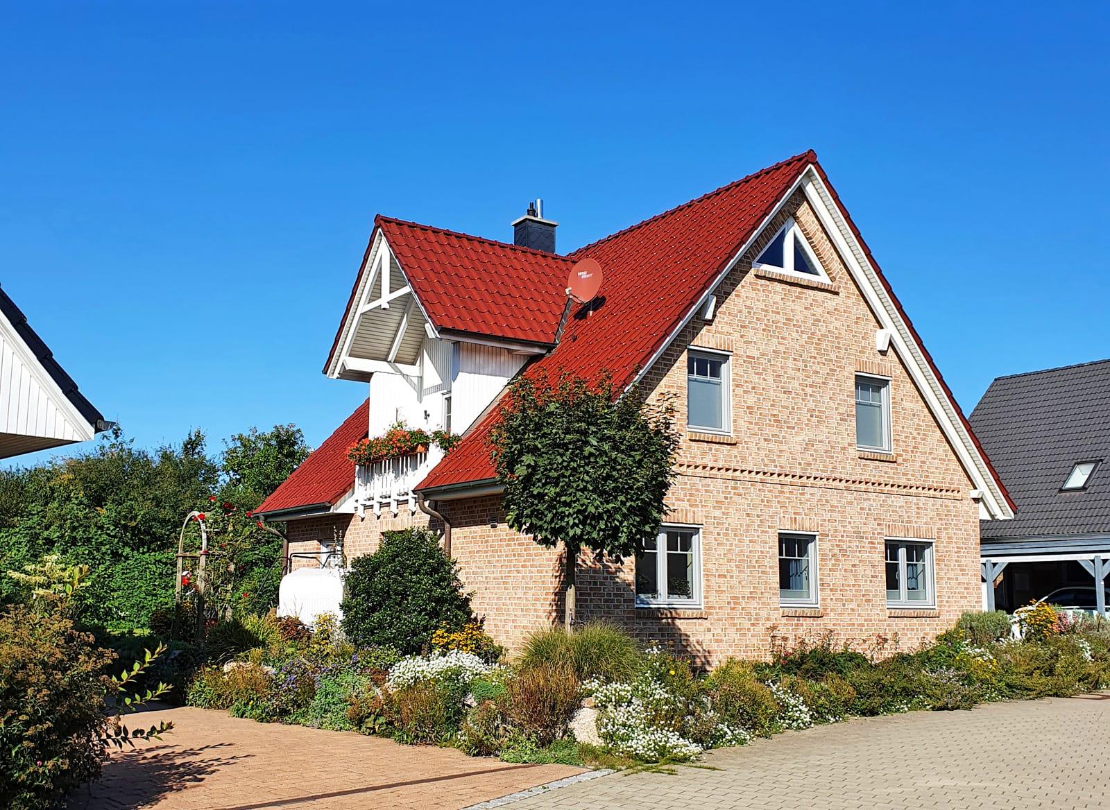 Ein Haus mit roten Dach, um dem sich viele kleine Pflanzen befinden.