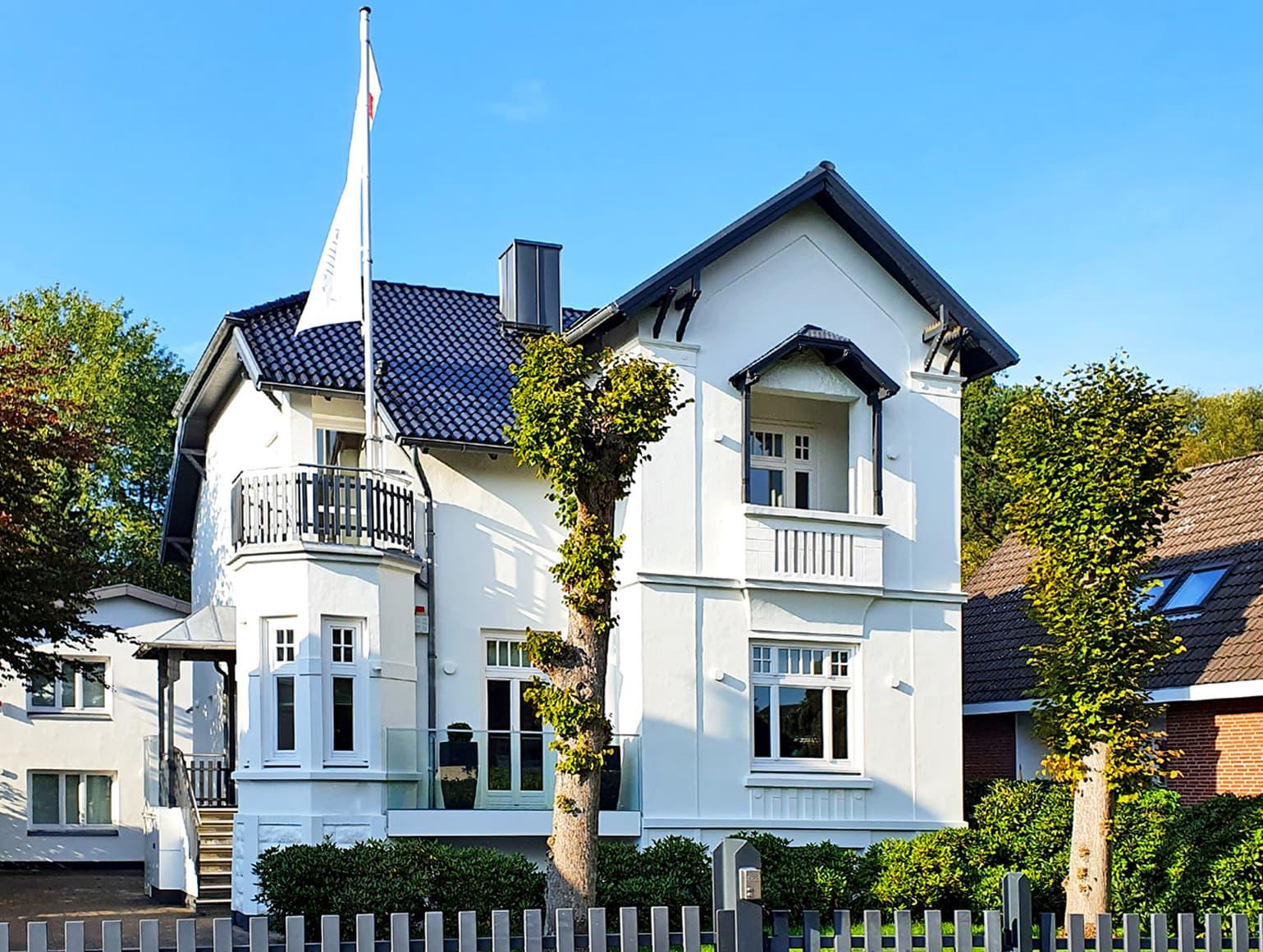 Weiße Villa mit blauem Dach und einer weißen Fahne.
